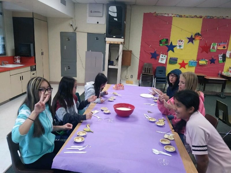 students sitting at a table making mini pies
