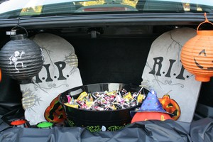 Car trunk decorated with headstones and a bowl of candy.