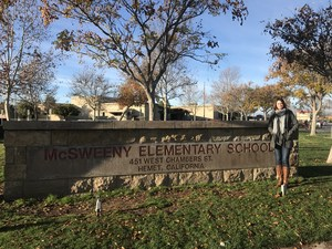 Jennifer Scott in front of the McSweeny Elementary School sign.