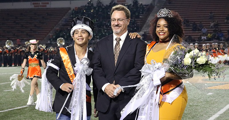 Homecoming queen and king being escorted by principal