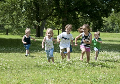 Kids running across a lawn.