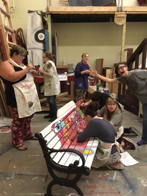 Art Club students work on a painting a bench that will be placed downtown Otsego for visitors.