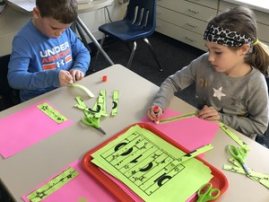 Students work on a puzzle with the number 100.
