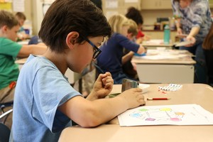 A student paints his color wheel.