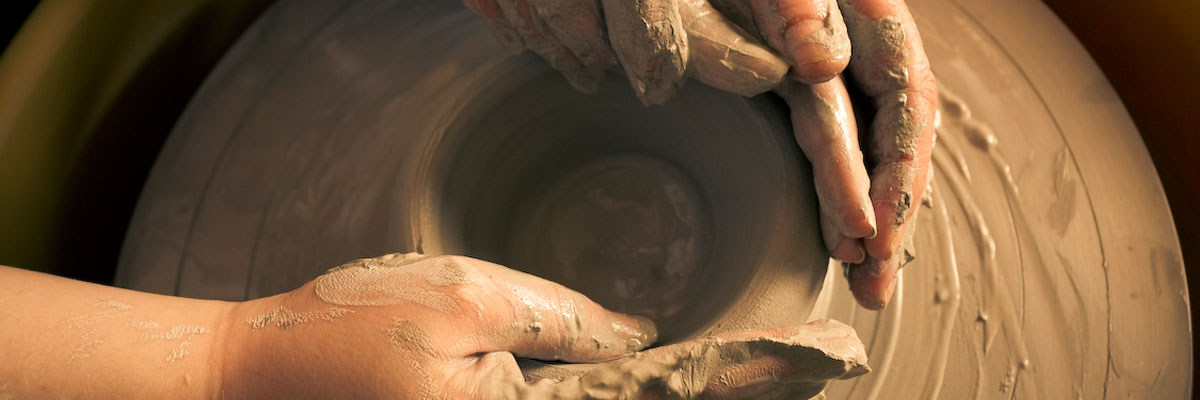 a student creates a piece of pottery on the wheel