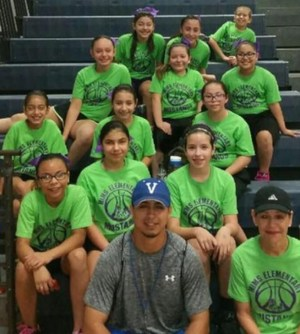 Girls basketball team with coach sitting in gym.