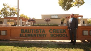 Greg Giroux in front of a Bautista Creek sign.