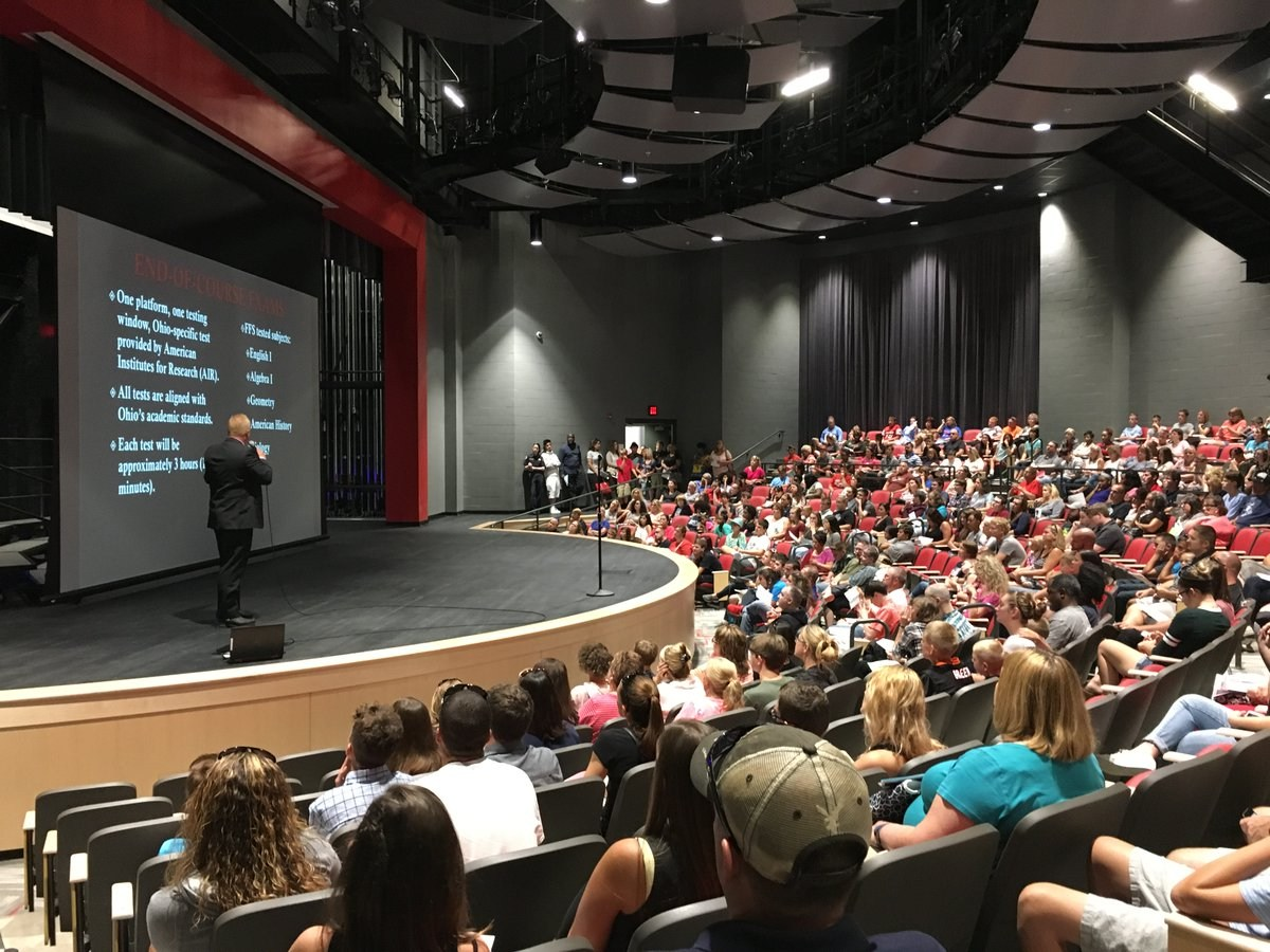 Mr. Berkemeier, Freshman School principal, is shown on stage addressing students and parents in an orientation meeting. The stage is in the new auditorium at the new school.