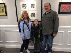 Student and family stands in front of his artwork.