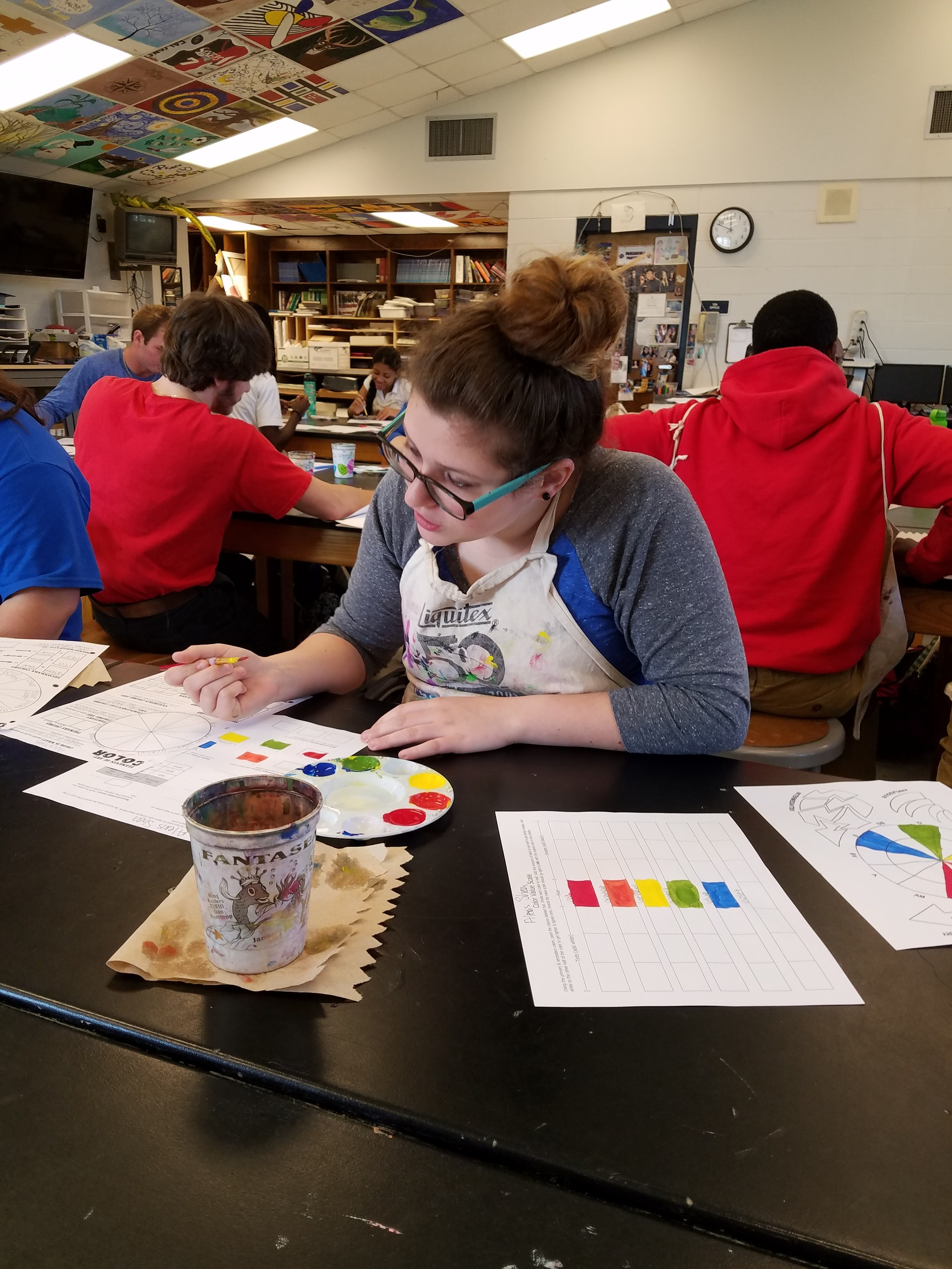 Student is applying knowledge of color by painting a color wheel