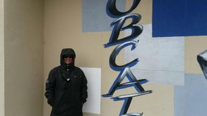 Teresa Haeckel bundled up in a jacket in front of a Hamilton K-8 sign.