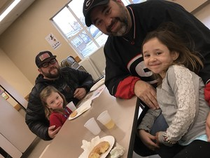 A student and guest celebrating at the kindergarten's Donuts for Dads event.