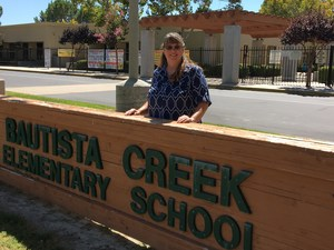 Margaret Stinson standing in front of a Bautista Creek sign