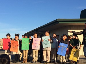 Kinder students showing an honesty sign