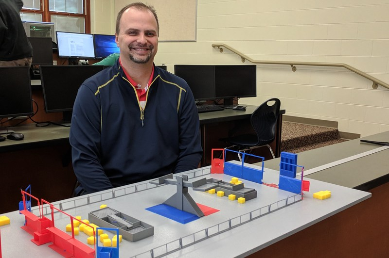 Michael Miller sits by a 3D printed model course for the HS robotics team.