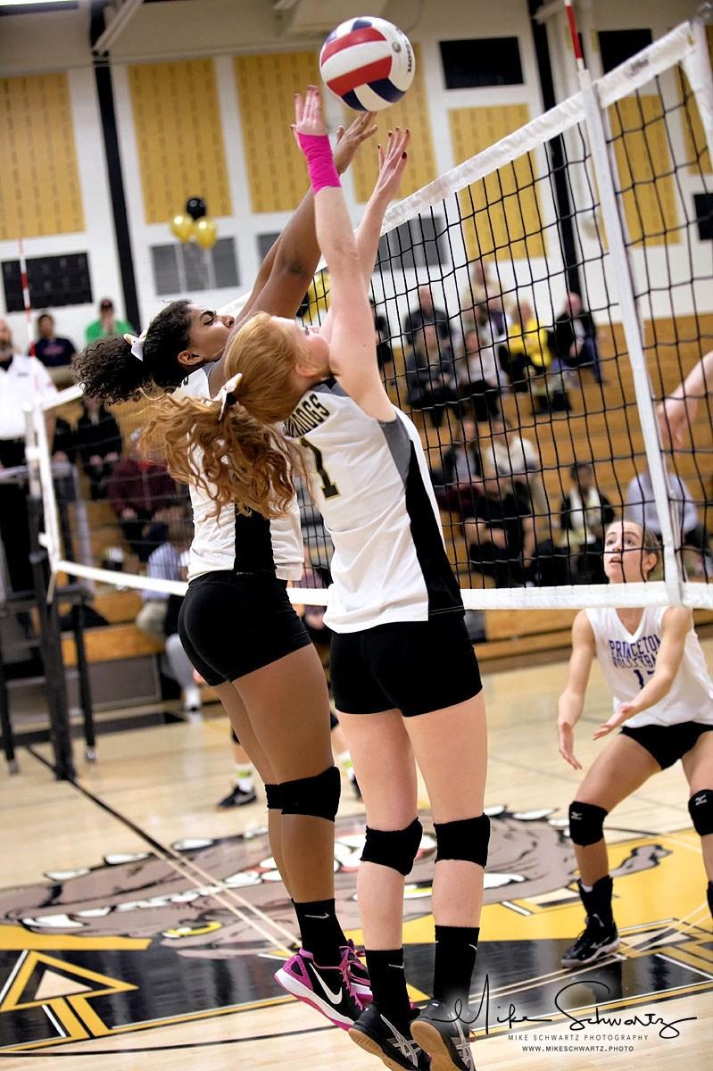 CHS girls volleyball players jump to block a shot