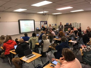 Teachers gathered in a classroom learning about Google Calendar.