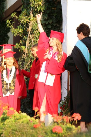 Hemet High student waiving as she receives her diploma