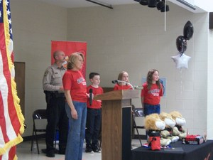 Principal, DARE officer, and students standing on stage.
