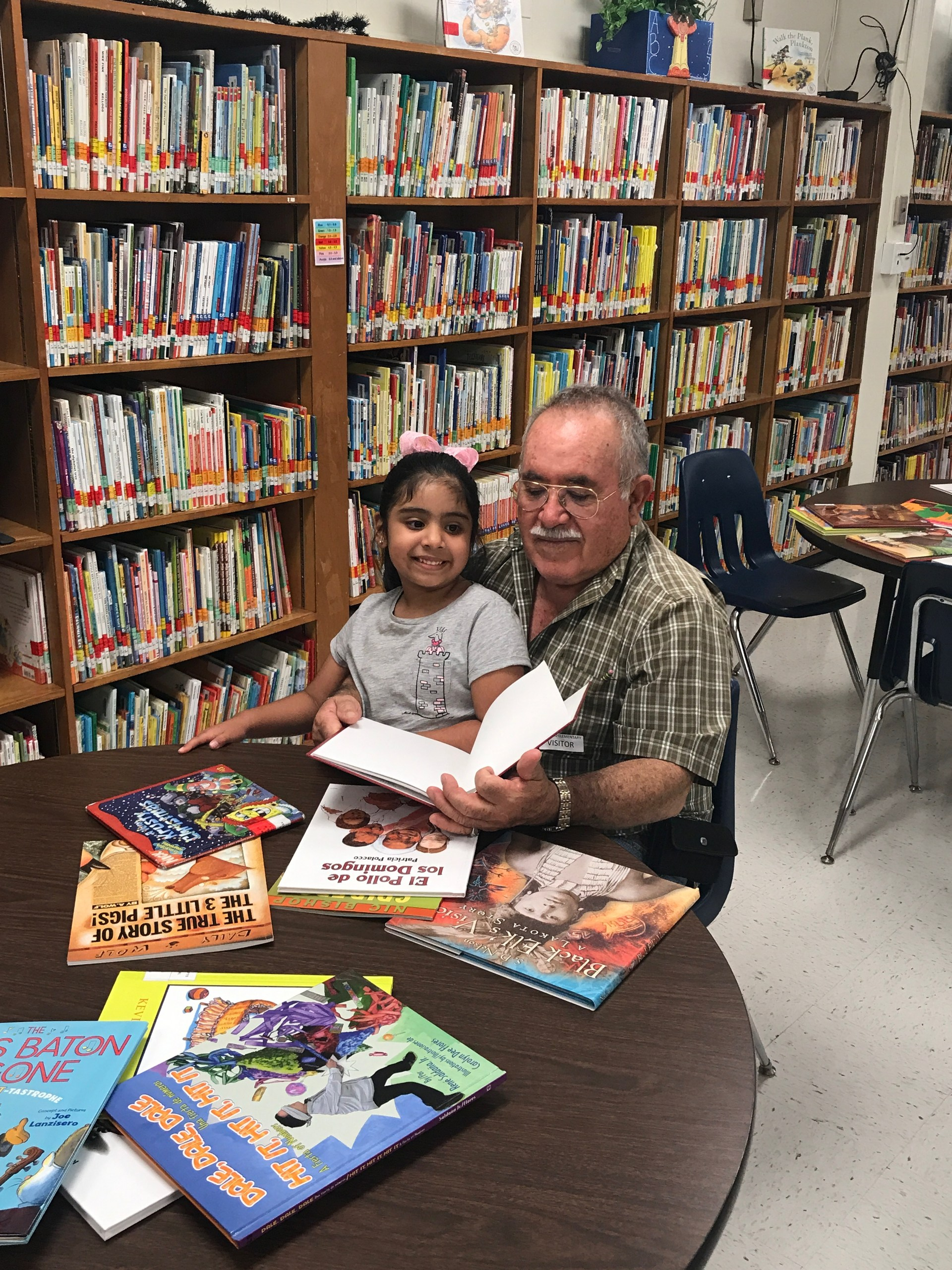 Grandfather reading to granddaughter in library