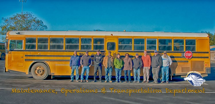 bus drivers standing in front of a bus