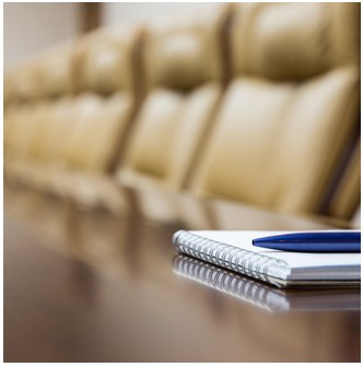 a board room table with empty seats and notepad