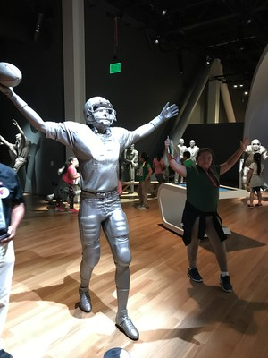 A student poses near a hall of fame statue