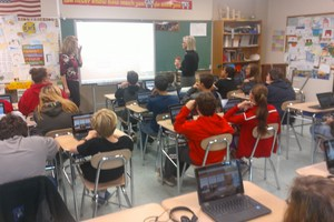 a classroom of students seated at desks face two teachers in front of a smartboard