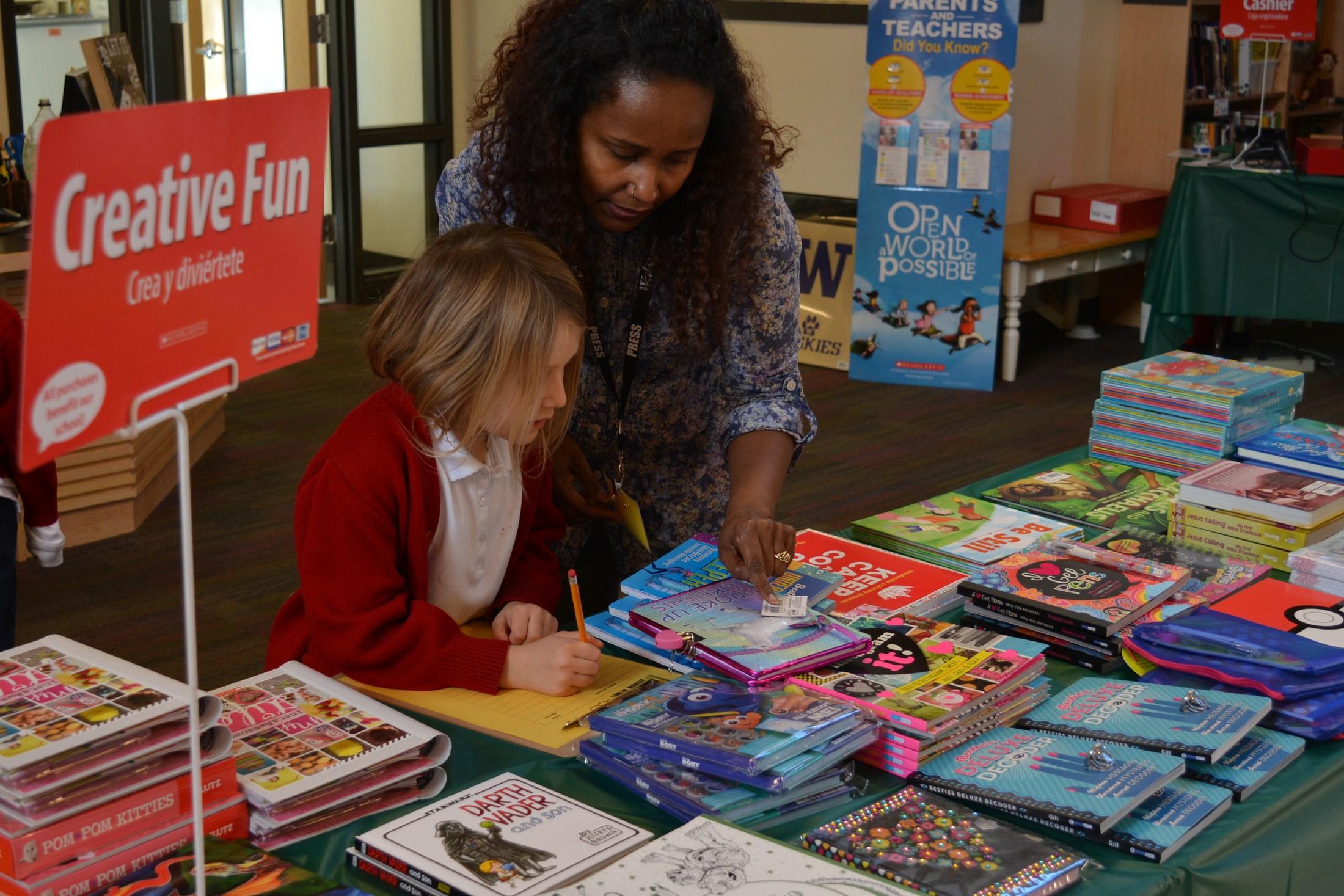 Parent volunteer helping student at book fair