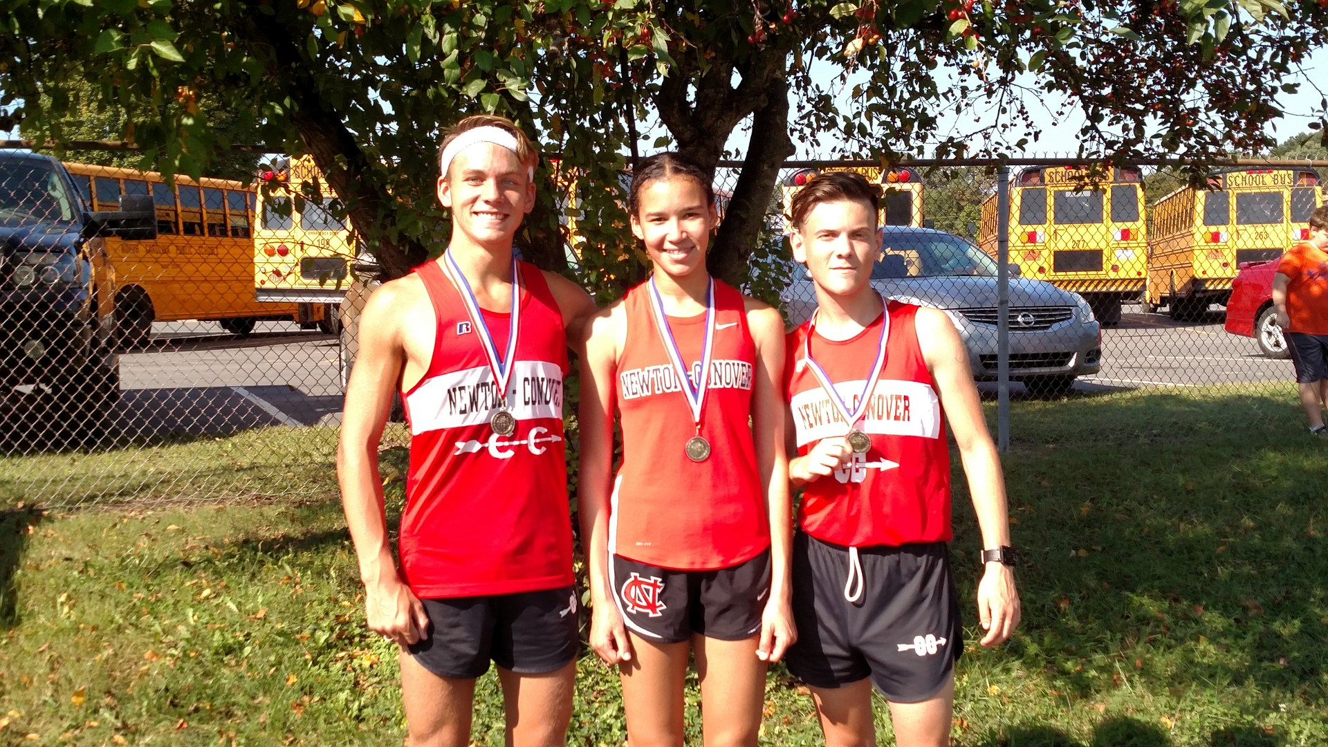 Caleb Henze, Mia  Macon, and Gunnar Taylor posing their medals after finishing in the top 10 at the Freedom Invitational XC meet on 9/16/17.