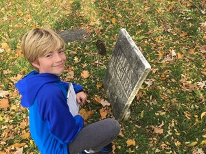 junior high student traces text from headstone in a cemetery