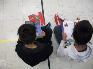 Two boys are sitting on the gym floor reading books.