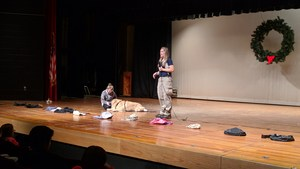 An OMS student pets Zeus on the stage after the demonstration.