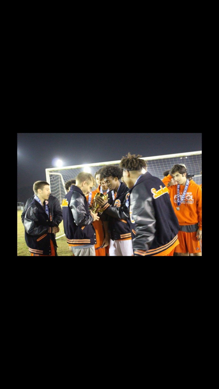 Boys Soccer team looks at the trophy they won