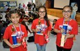Walnut Elementary School fifth-graders Ariana Ramirez, left, Andrea Salazar and Leslie Hernandez display their first-, second- and third-place cars after the school's first-ever Pinewood Derby on March 9.