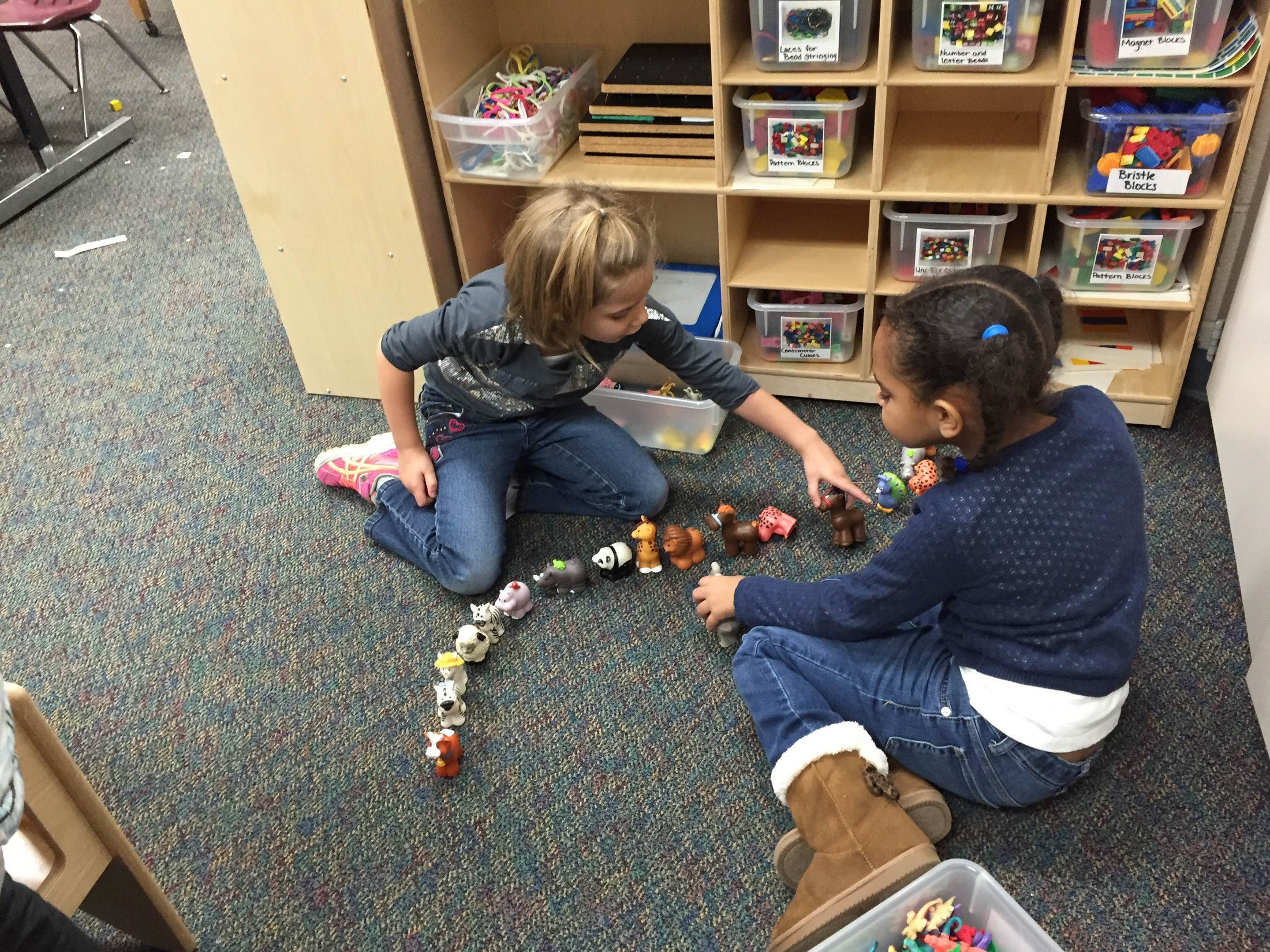 Two girls constructing a train of animals.