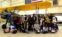 Photography Students pose by plane