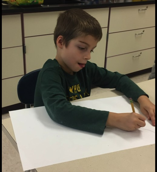 Elementary student sits at desk drawing on white paper