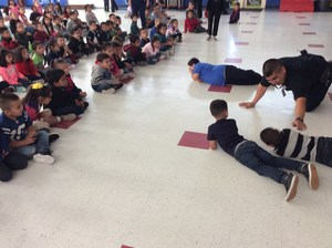 Students in gym with firefighters practicing routine on floor.