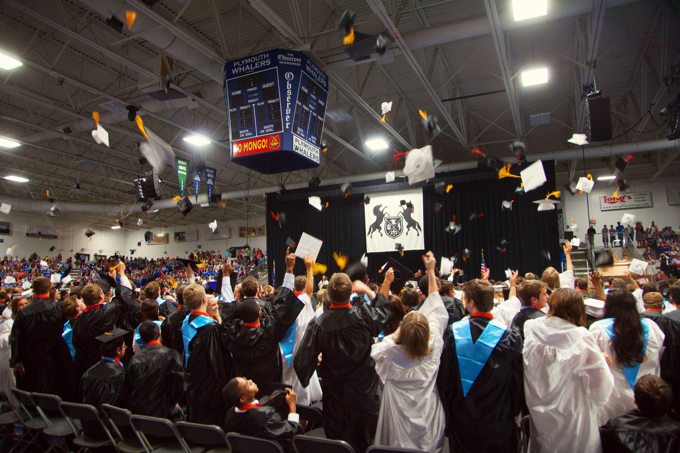 Northville High School graduates toss their graduation caps in the air.