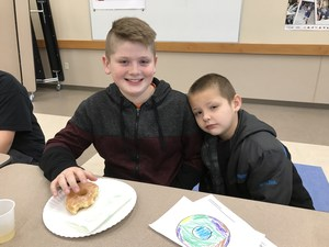 A kindergarten student and his 5th grade buddy at Donuts for Dads.
