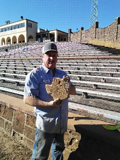 Maintenance worker holding the Texas shaped rock