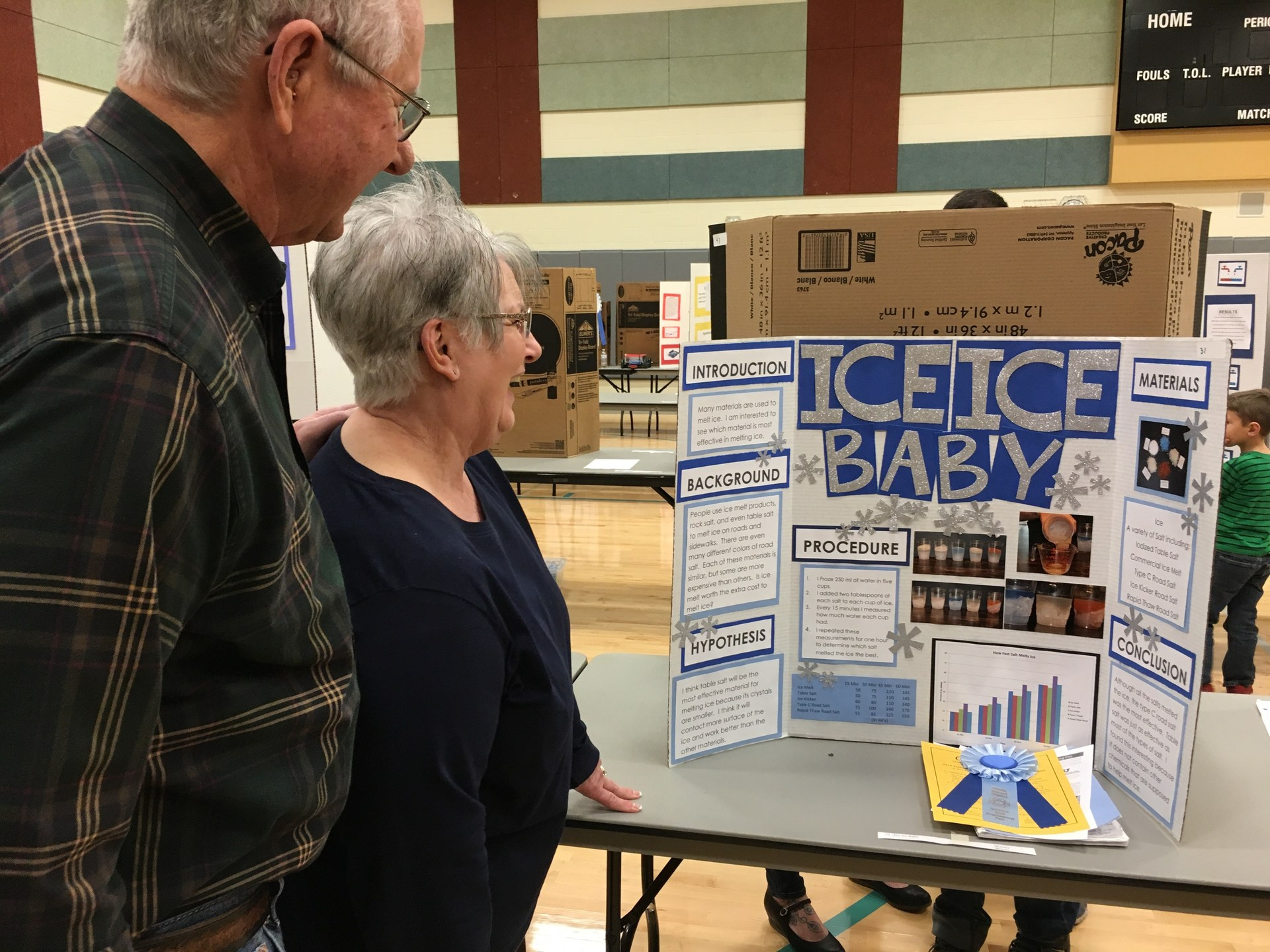 Grandparents looking at a Science Fair Project