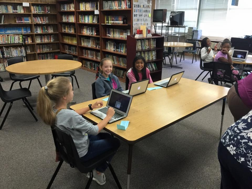 Students using MacBooks in the Library
