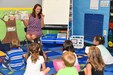 Students reading a book with an East Valley Elementary teacher during kindergarten orientation for the 2017-18 school year.