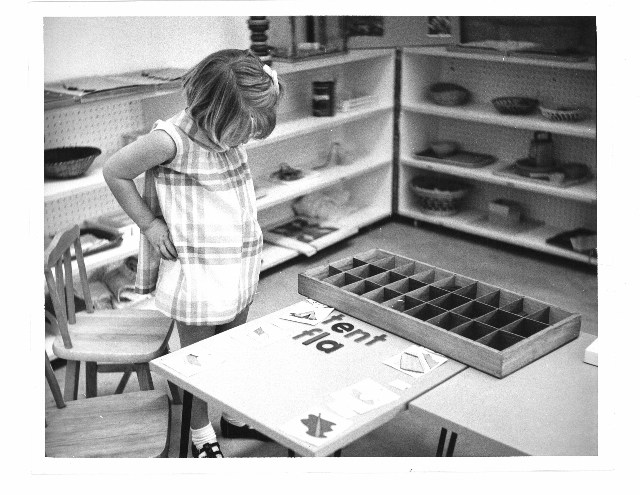 Picture of young girl staring at wooden language work in montessori classroom.