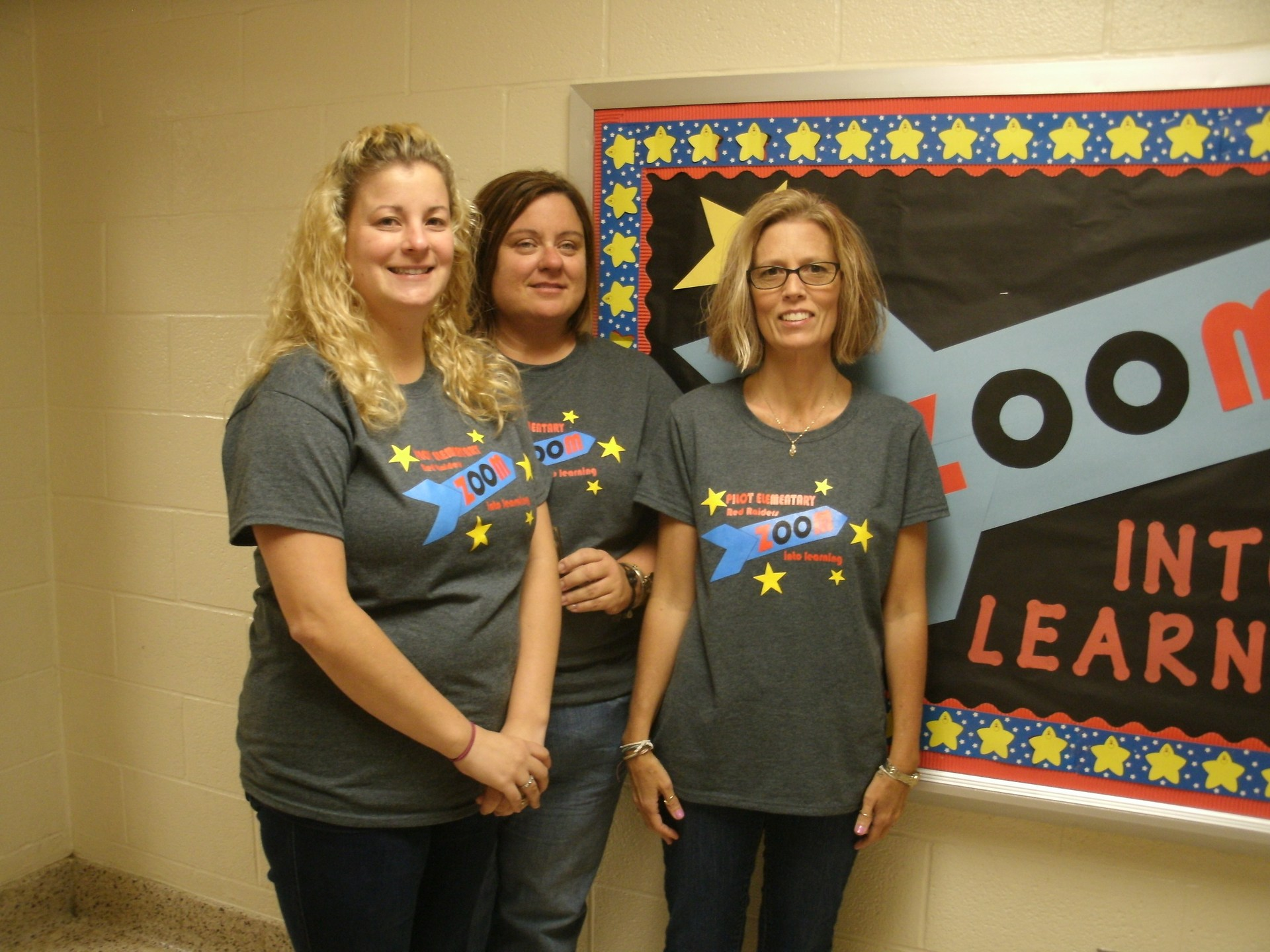 The preschool teacher and two preschool instructional assistants are standing in front of a bulletin board.