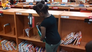 A student chooses a book.