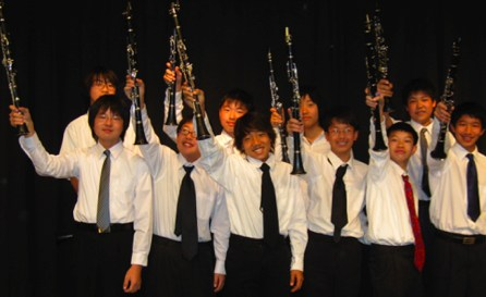 Music students holding up thier instruments.