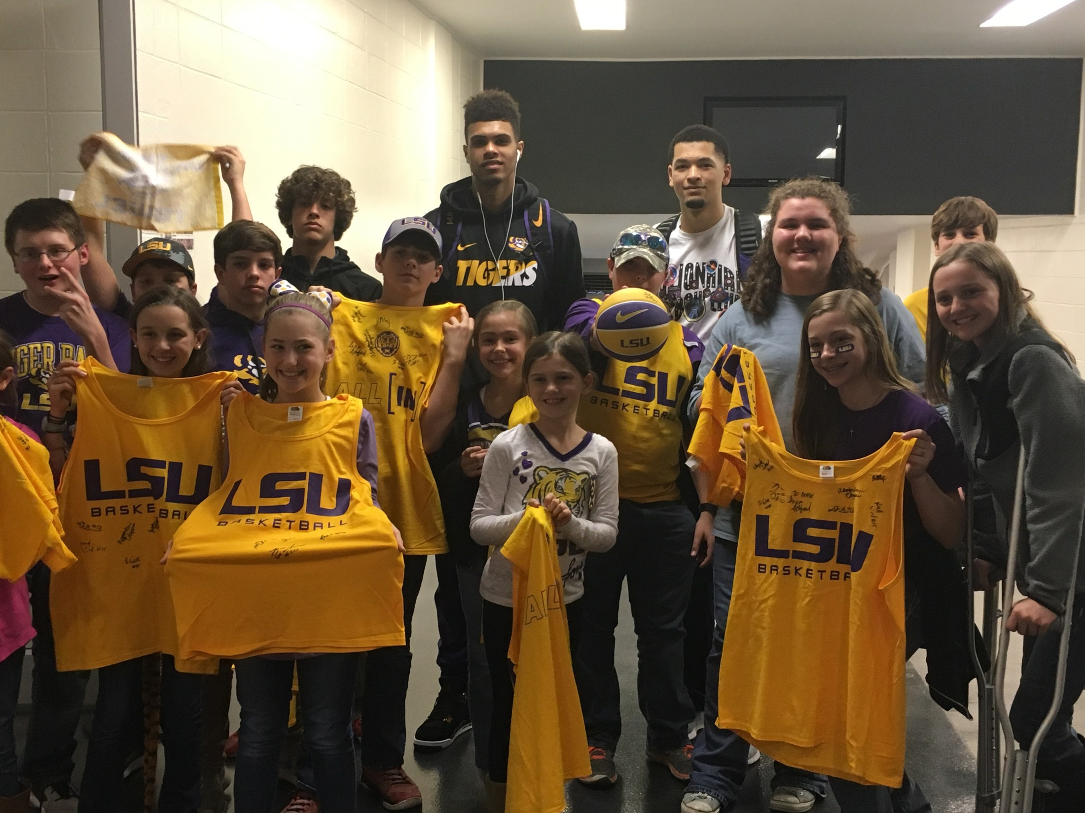 KSE boys and girls team taking a group pic with a few LSU players